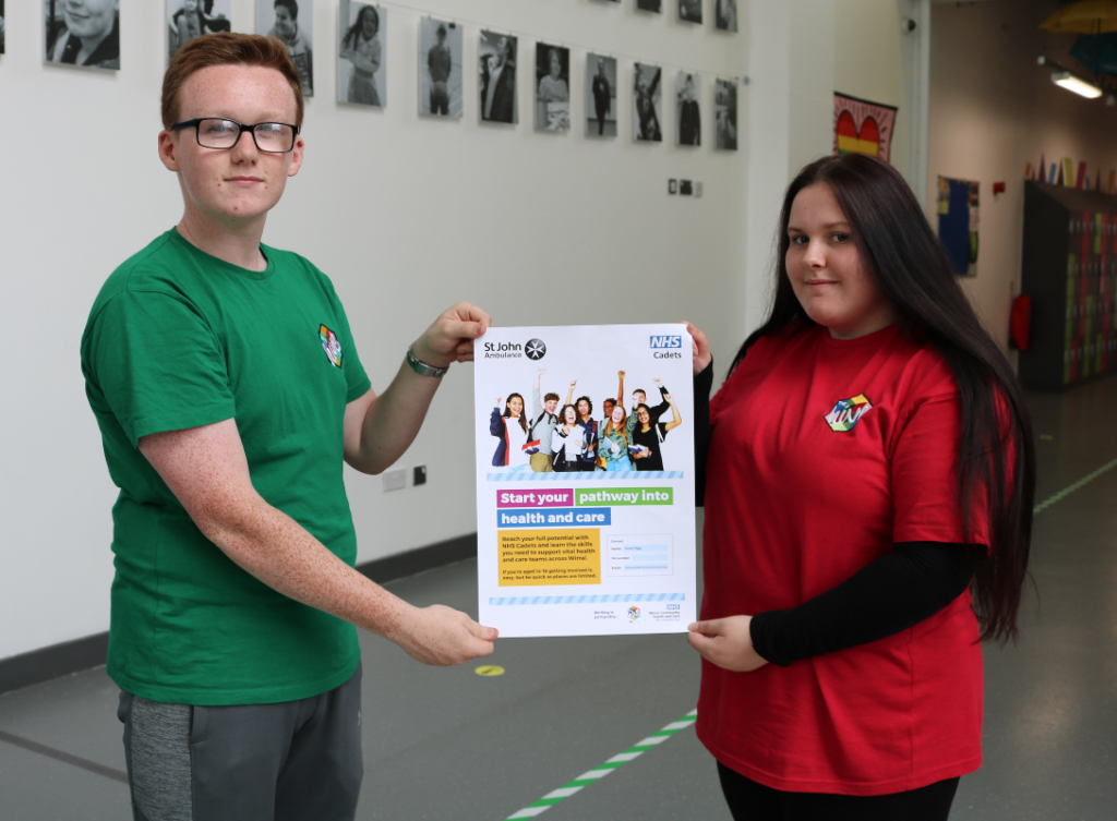 Two young people at The Hive Youth Zone holding poster about the Wirral NHS Cadets programme